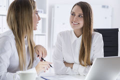Two women discussing private issues in office Stock Photos