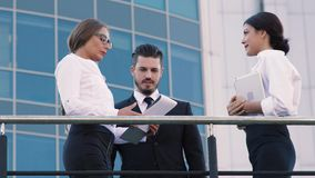 Two women discussing their plans and projects and business man comes up to them to keep the conversation. Two women discussing their plans and projects. Business stock footage