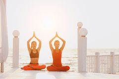 Two women do yoga at sunrise near the sea. A two women do yoga at sunrise near the sea Royalty Free Stock Images