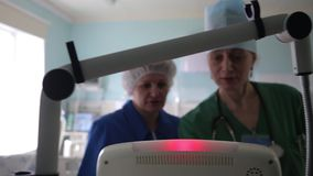 Two women doctors use a medical computer device.4K