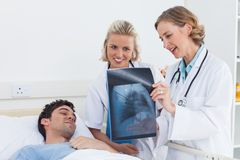 Two women doctors showing x-ray to a patient Royalty Free Stock Photos