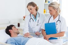 Two women doctors talking  to a patient Stock Photo