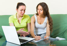 Two women with documents and laptop indoor Royalty Free Stock Photography