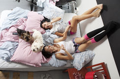 Two women with dog in bed smiling Stock Photos