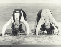 Two women doing backbends on the beach Stock Image