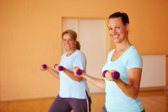 Two women doing dumbbell exercises Stock Images