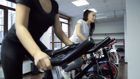 Two women doing exercise on stationary bike in fitness studio. Brunette woman with long picked tail hair white t-shirt, grey pants, white sneakers pedaling in stock footage