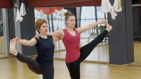 Two women are doing extended hand-to-dig-toe pose on yoga class in modern gym, slow motion. Mature woman in black sportswear and young lady in red top are stock footage