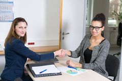 Two women doing a handshake during a meeting Royalty Free Stock Photo