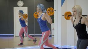 Two women doing lunges with barbell in gym. Young female stand with free weight on shoulders, then take step back, crouching to floor level and returning to stock video footage