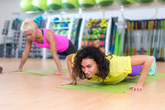 Two women doing push-ups on mats exercising in a gym.  royalty free stock photos
