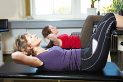 Two women doing sit-ups Stock Images