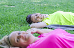 Two women are doing sport on fresh grass green. Royalty Free Stock Photos