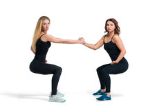 Two women doing squats helping each other isolated Stock Images