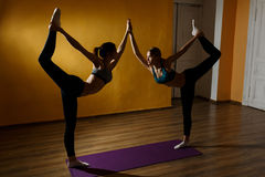 Two women doing stretching exercises. In sports hall Stock Photos