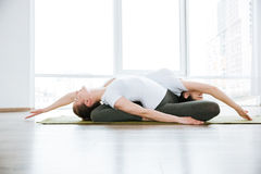 Two women doing stretching exercises in yoga center Royalty Free Stock Photos
