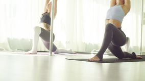 Two women doing stretching yoga exercises in studio. Yoga class. Two women doing stretching yoga exercises in studio stock video