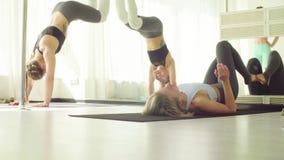 Two women doing warm-up gymnastic exercises. In studio stock video