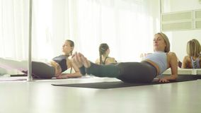 Two women doing warm-up gymnastic exercises. For the abdomen stock video