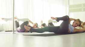 Two women doing warm-up gymnastic exercises. For the abdomen stock footage