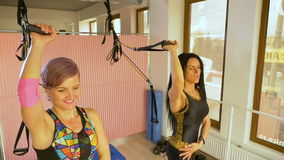 Two women doing weight loss exercise for arms using elastic cable equipment stock video footage