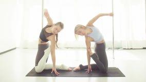 Two women doing yoga asanas in studio. Yoga class. Two women doing yoga asanas in bright studio together synchronously stock video footage