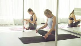 Two women doing yoga breathing in studio. Yoga class. Two women doing yoga breathing - agnisar dhauti fire purification stock footage