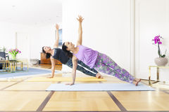 Two women doing yoga at home Stock Image