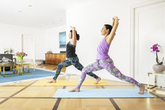 Two women doing yoga at home Stock Images