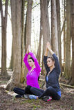 Two women doing yoga in the middle of the woods Royalty Free Stock Photos