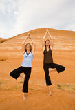 Two Women Doing Yoga Orange Rocks Royalty Free Stock Image