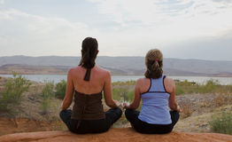 Two Women Doing Yoga at Sunset Stock Image