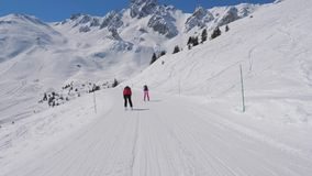 Two Female Skiers Skiing Down The Ideal Slope Of The Mountain In Winter. Two women downhill skier down the ideal ski slope. Skiing on the track against the stock video footage
