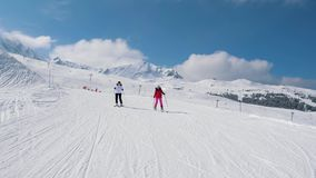 Two Woman Skiers Skiing Down The Ideal Slope Of The Mountain In Winter. Two women downhill skier slowly down the ideal ski slope. Skiing on the track against the stock video