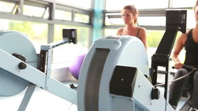 Two women drawing on row machine. In gym stock video footage