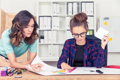 Two women drawing a scheme Royalty Free Stock Photos