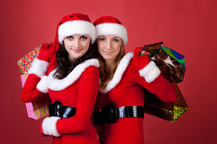 Two women in dressed as Santa, with shopping bags Royalty Free Stock Photo