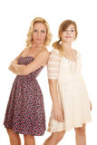 Two women in dresses back to back serious Stock Photography