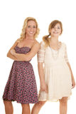 Two women in dresses back to back side smile Royalty Free Stock Images