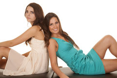 Two women dresses sit backs together Royalty Free Stock Photo