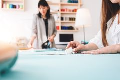 Two women dressmaker making designer clothing in showroom. Young female professional seamstress working at sewing. Two women dressmaker making designer clothing stock photo