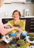 Two women with dried herbs Royalty Free Stock Photos