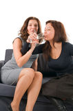 Two women drink champagne sitting on a sofa Royalty Free Stock Image
