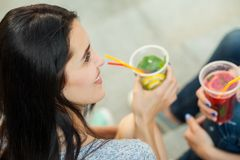 Two women drink cold cocktails. Two women talk and drink cold cocktails, pretty friends, nice girlfriends walk around the city and drink lemonade. close up Royalty Free Stock Images