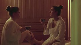 Two women drink herbal tea in the spa center spa they will not have dehydration.