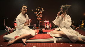 Two women drink herbal tea and talk. stock footage