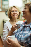 Two women drink tea on balcony Royalty Free Stock Photo