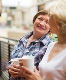 Two women drink tea on balcony Stock Photos