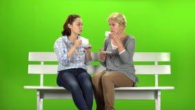 Two women drink tea and talk. Green screen. Two women sit on a wooden bench and drink tea and talk. Green screen stock video