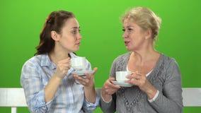 Two women drink tea and talk. Green screen. Two women sit on a wooden bench and drink tea and talk. Green screen stock footage